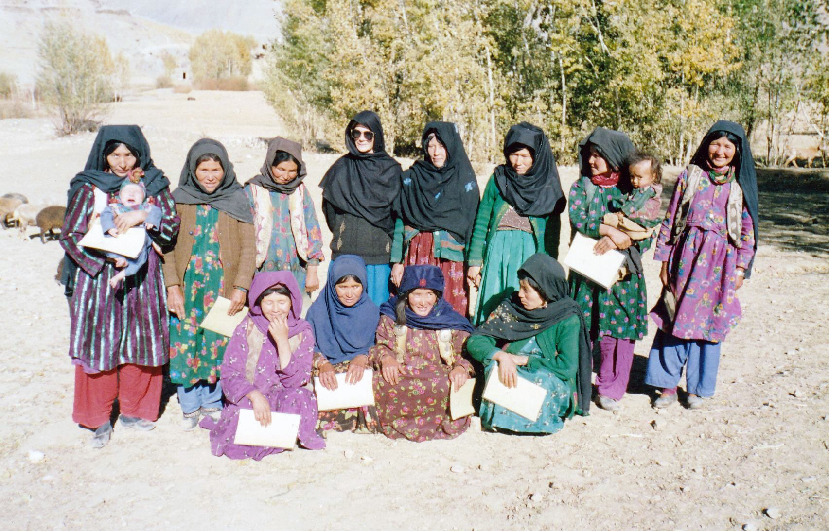 Photograph shows a a group of Afghan women with certificates of completion of a healthcare course.