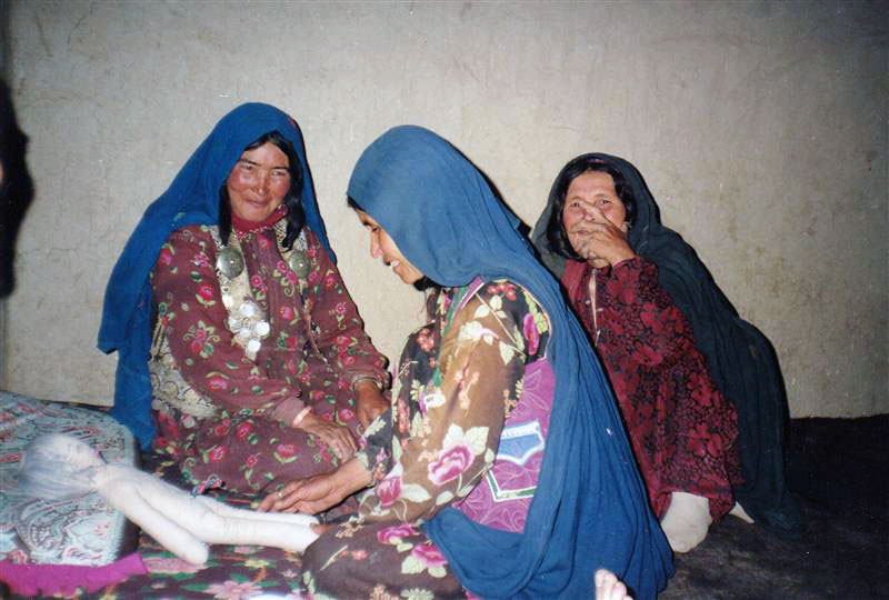 Photograph shows three Afghan women training to be healthcare workers.