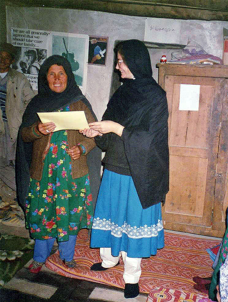 Photograph shows author Mary Smith handing a certificate of completion of a healthcare course to an Afghan woman.