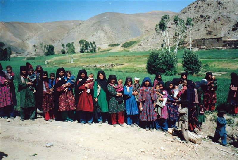 The photograph shows a line of Afghan women waiting for an antenatal clinic.