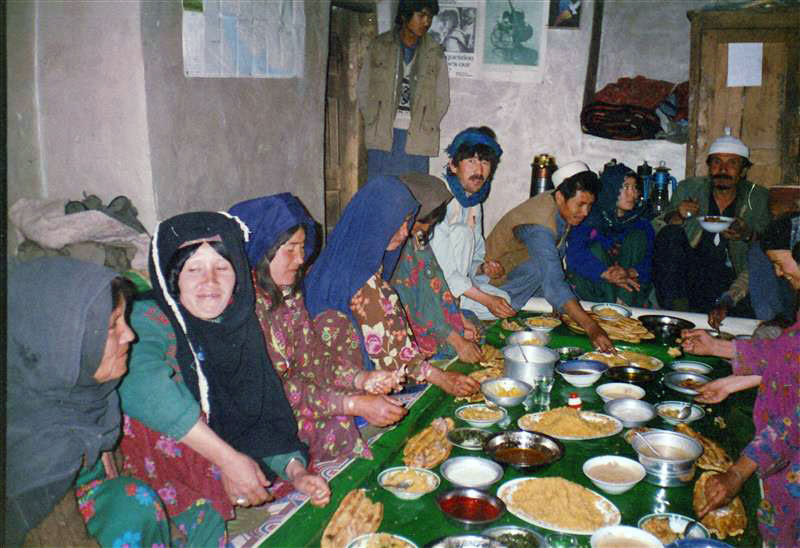This photograph shows a group of Afghan woman eating lunch.