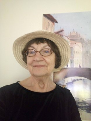 Image is of Elizabeth Merry wearing a hat and standing in front of a painting of a bridge.