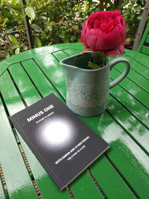 Image of green table, poetry book, and red peony