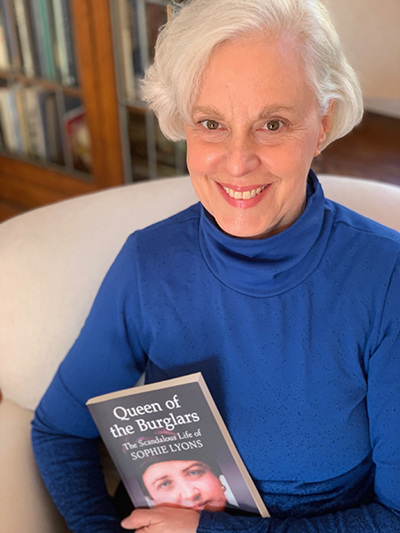 The image shows author Shayne Davidson holding a copy of her book Queen of the Burglars.
